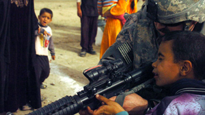 PHOTO A U.S. Army captain gives an Iraqi boy a peek through the ACOG on his M-4 carbine assault rifle in the village of Sudoor, Diyala, Iraq