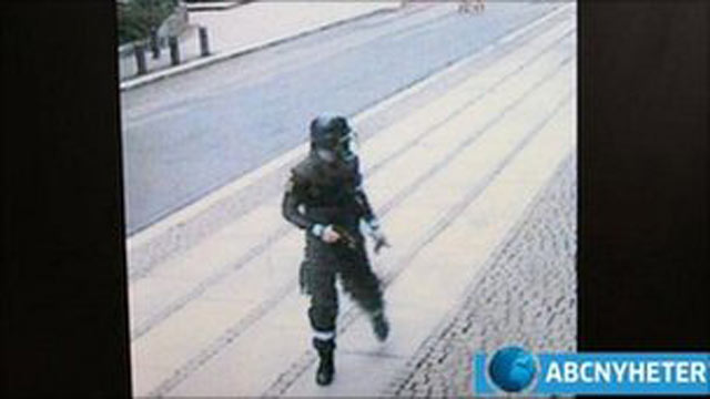 PHOTO:Anders Behring Breivik is filmed by CCTV cameras wearing a police uniform and holding a gun as he walks away from a car after placing a bomb in Oslo.