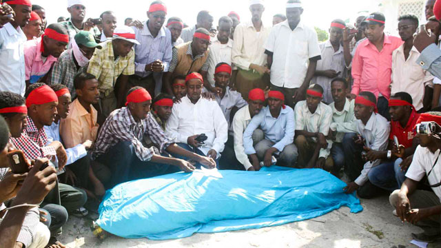 PHOTO: Fellow journalists crowd around the body of Abdisalam Hiis who was murdered in Mogadishu on December 18, 2011.