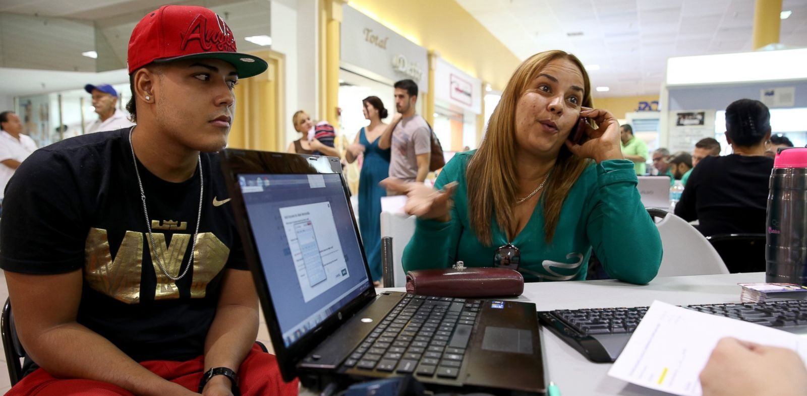 PHOTO: Carlos Salvador, left, sits with his mother, Yadelmis Ramirez, as she speaks with an insurance agent from Sunshine Life and Health Advisors as they purchase health insurance under the Affordable Care Act on February 1, 2014.