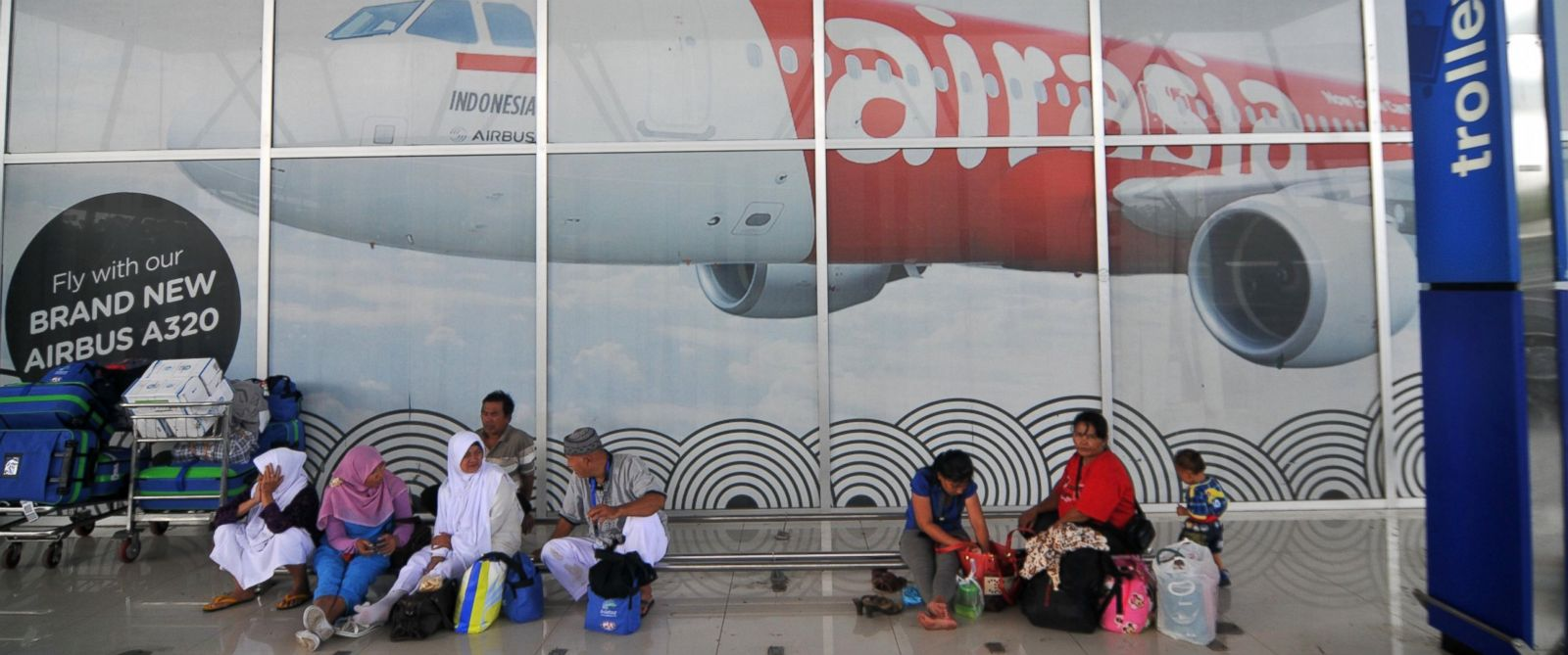 PHOTO: People wait for their families in front of a Air Asia billboard