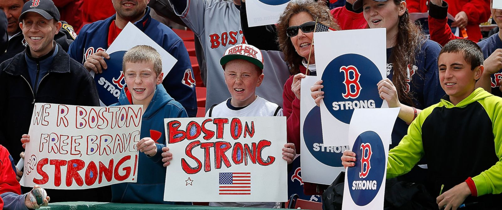 PHOTO: Fans hold a sign to honor the Marathon bombing victims, before a game against the Kansas City Royals at Fenway Park, April 20, 2013, in Boston.