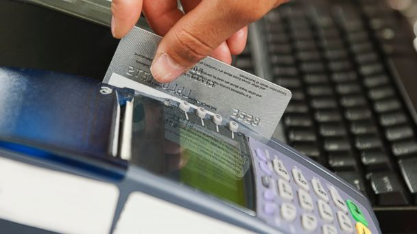 PHOTO: In this stock image, a woman is pictured swiping her debit card for a purchase.
