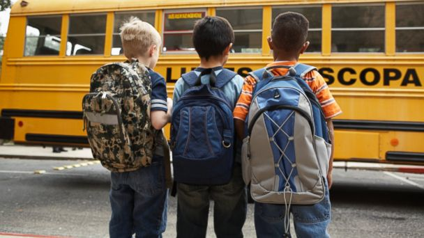 PHOTO: Three boys wearing backpacks stand near a school bus in this stock photo.