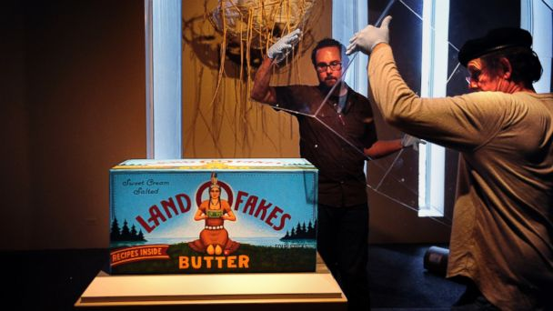 PHOTO: Installation assistant Kevin Hester helps exhibition specialist John Lupe seat a protective cover for David Bradleys Land O Bucks, Land O Fakes, Land O Lakes art work in the DAMs American Indian galleries.