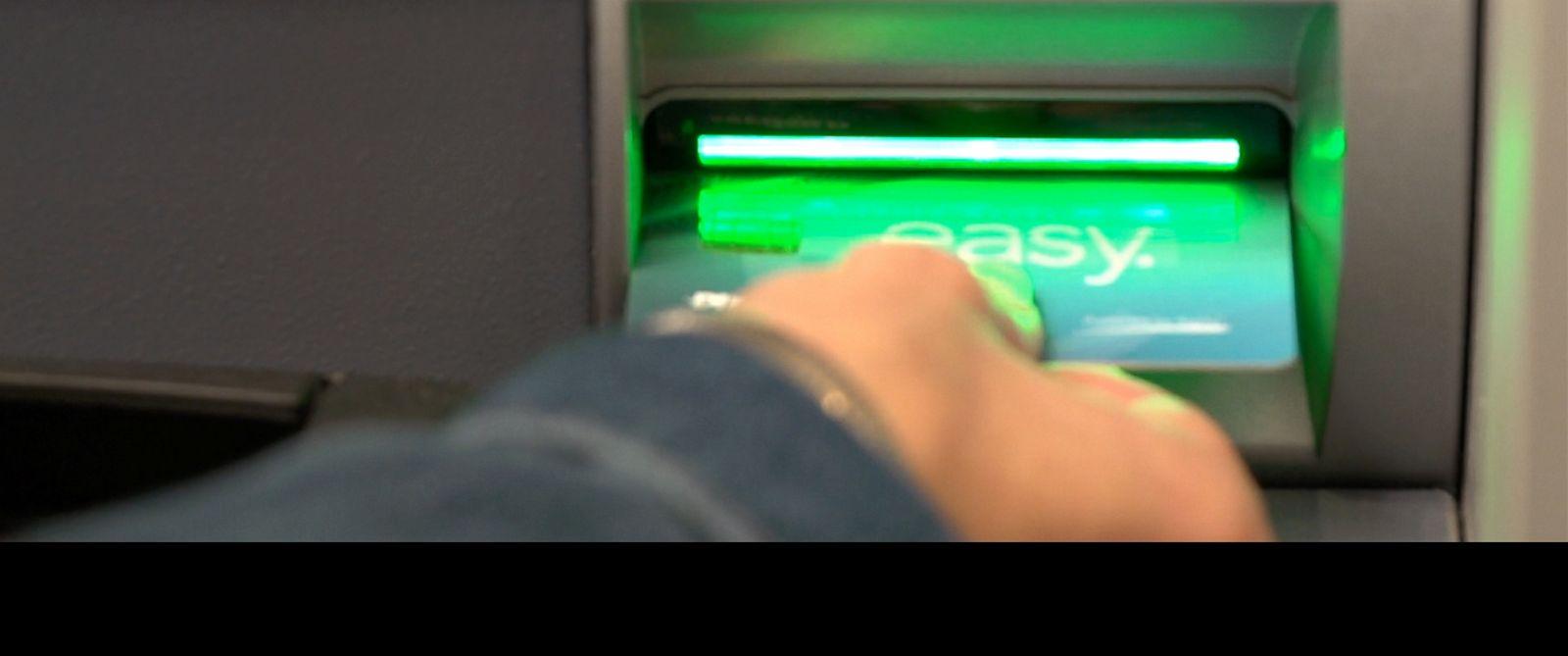 PHOTO: A bank customer swipes his card sideways.
