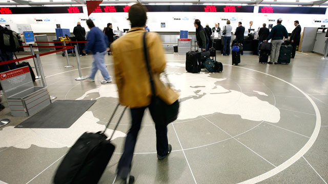 PHOTO: In this file photo, passengers approach the check-in counter at the Minneapolis St. Paul International Airport in Minneapolis.