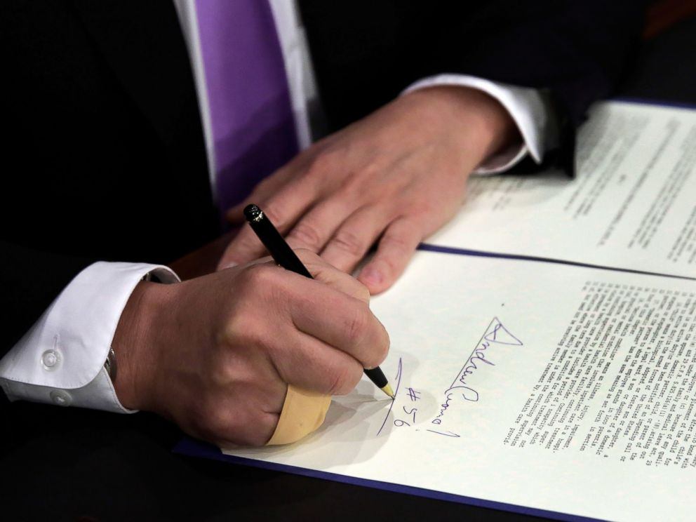 PHOTO: New York Gov. Andrew Cuomo, signs a law that will gradually raise New Yorks minimum wage to $15, at the Javits Convention Center, in New York, April 4, 2016.