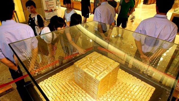 PHOTO: Chinese girls look at a tower of gold bars worth 38 million USD displayed at a shopping mall in Beijing on July 30, 2010.