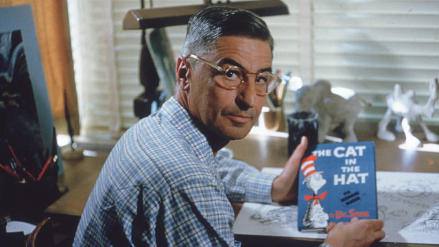 PHOTO: Theodor Seuss Geisel sits at his drafting table in his home office with a copy of his book, 'The Cat in the Hat', La Jolla, California, April 25, 1957.