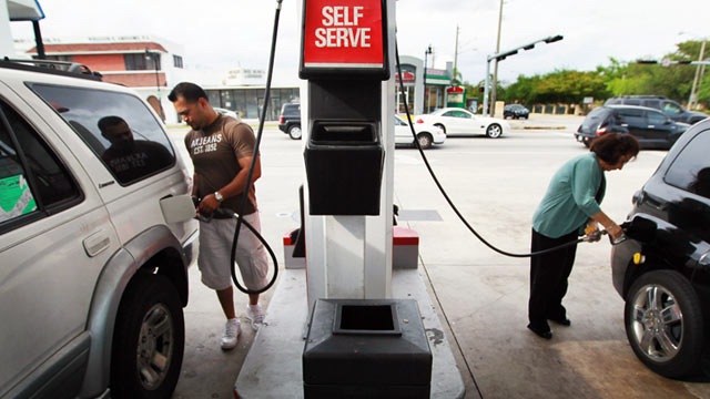 PHOTO: Two people pump gas at the Ugas station, March 6, 2011, in Miami.