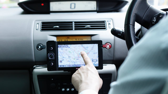 PHOTO: A businessman uses GPS navigation system in his car.