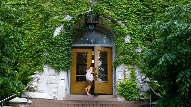 PHOTO: College student walking through door of Northwestern University building.