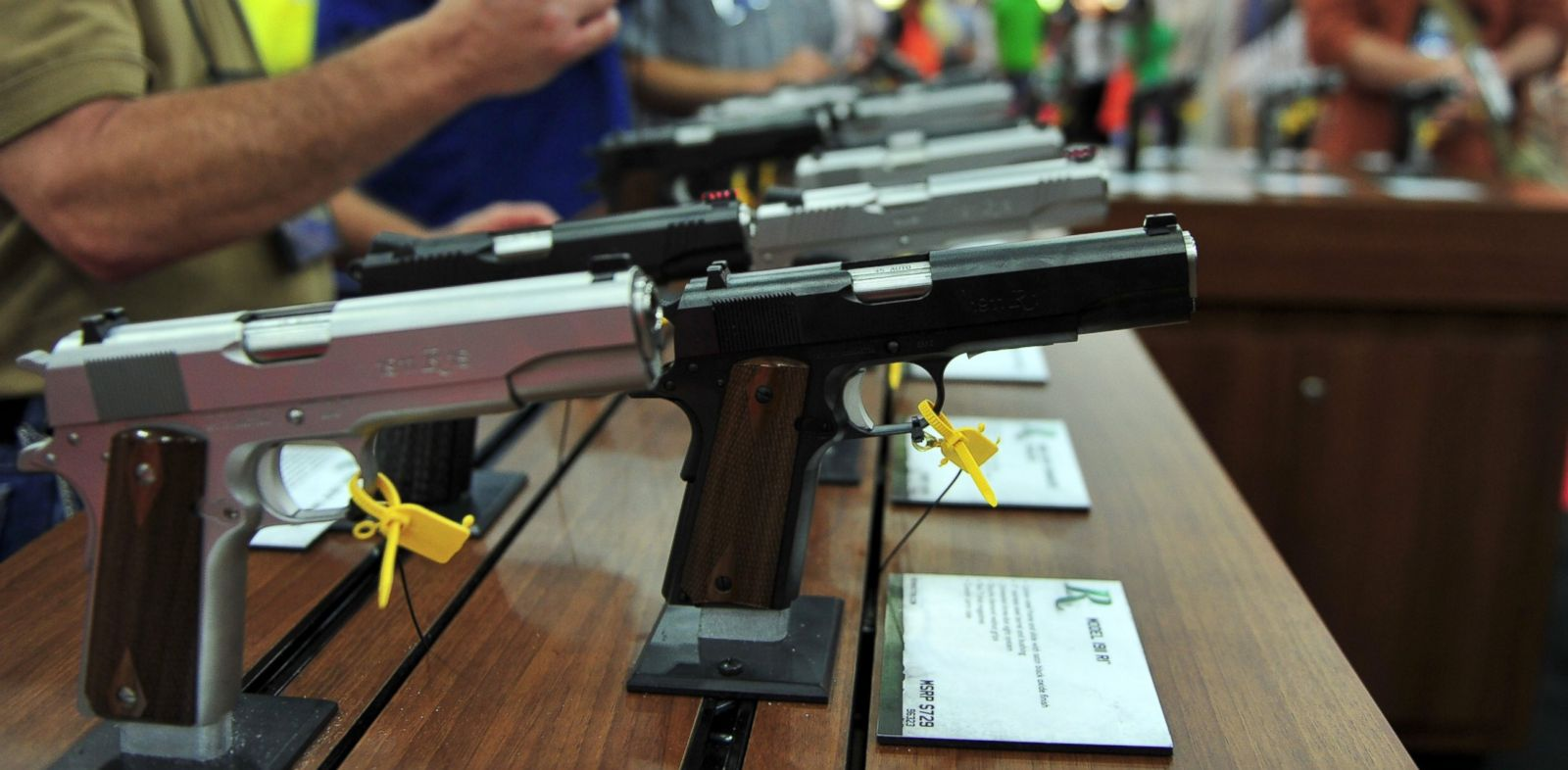 PHOTO: Convention goers look at various models of Ruger 1911 model semi-automatic pistols during the National Rifle Association convention at the George R. Brown Convention Center May 4, 2013 in Houston, Texas.