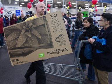 PHOTO: A Best Buy employee carries a flat screen TV as Black Friday shoppers stand in the check-out area, Nov. 28, 2013, at the Best Buy store in Fairfax, Va.