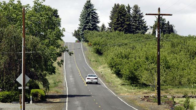 PHOTO: A car drives down Young Grade Road along G&G Orchards near Yakima, Washington.