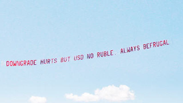 """PHOTO:""""Downgrade hurts but USD no ruble. Always be frugal,"""" was the message on the banner over the Financial District, August 11, 2011, paid for by Jon Lal, 43, a Boston-based businessman who runs a website, befrugal.com."""