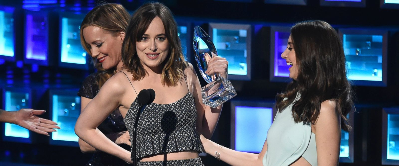 "PHOTO: Dakota Johnson, left, accepts the award for favorite dramatic movie actress for ""Fifty Shades of Grey"" from Alison Brie at the Peoples Choice Awards at the Microsoft Theater on Jan. 6, 2016, in Los Angeles."