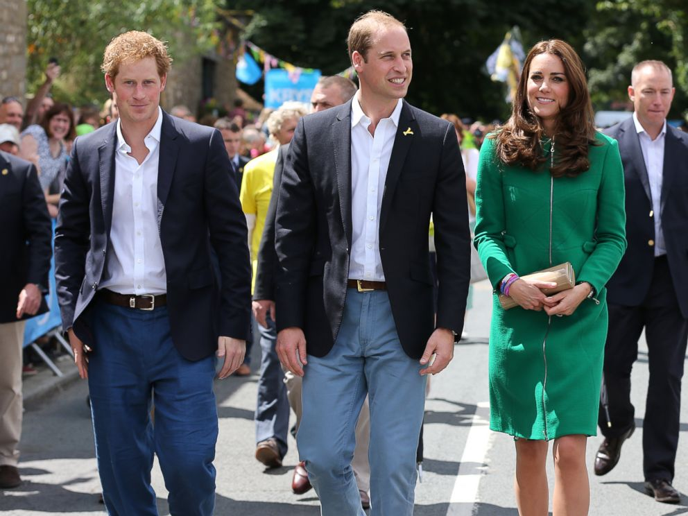 PHOTO: (L-R) Prince Harry, Prince William and Kate, Duchess of Cambridge walk along the street to celebrate the start of the Tour de France in Yorkshire at West Tanfield, England, Saturday, July 5, 2014.