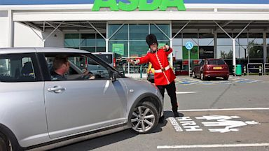 PHOTO: A man dressed as a member of the queens guard poses beside a parking space reserved for a prospective prince or princes at Asda supermarke