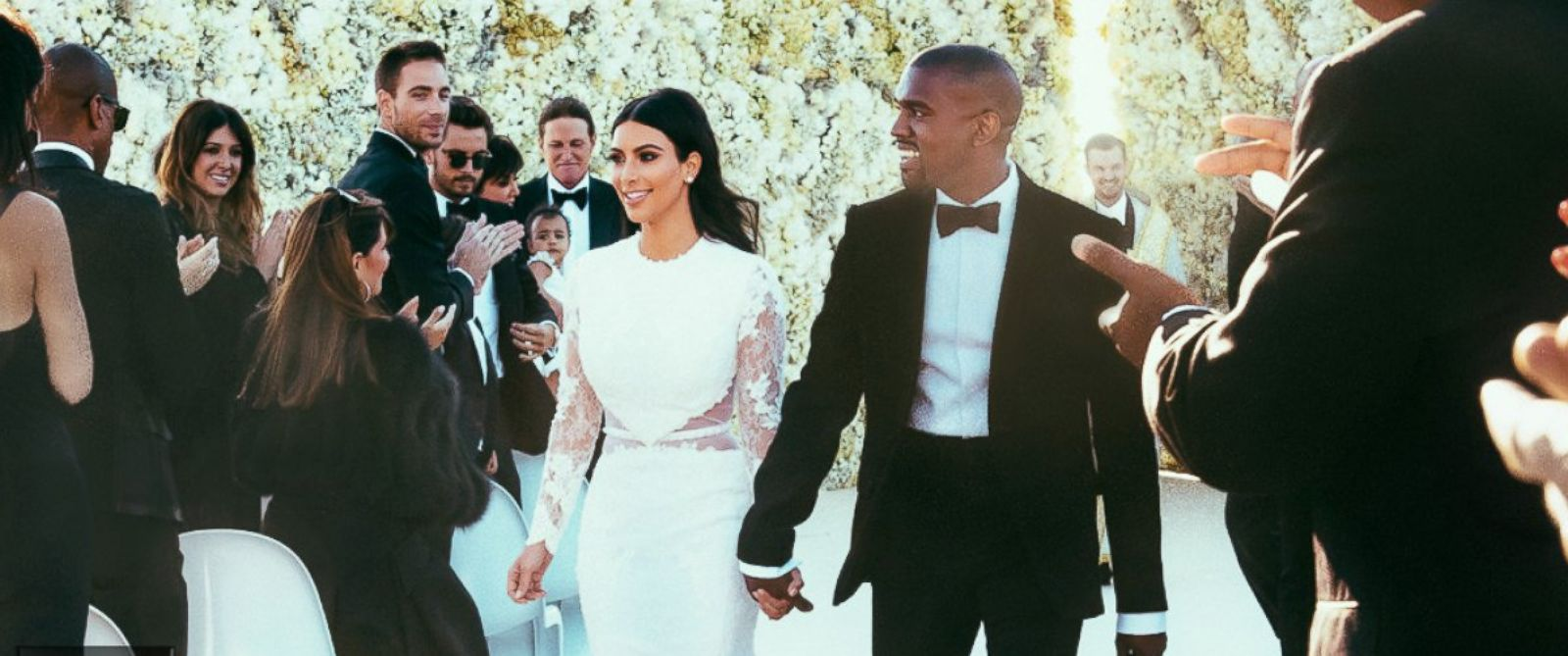 """PHOTO: Newlyweds Kanye West and Kim Kardashian walk down the aisle as friends and family look on at the Forte di Belvedere in Florence, Italy, May 24, 2014. <a href=""""http://www.eonline.com/news/545405/kim-kardashian-and-kanye-west-s-first-photos-as-a-marr"""