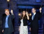 """PHOTO: From left: Prince Harry, Kate the Duchess of Cambridge, and Prince William, raise their wands on the film set used to depict Diagon Alley in the Harry Potter Films during the inauguration of """"Warner Bros. Studios Leavesden"""" near Watford, England, A"""