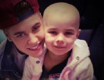PHOTO: Justin Bieber poses with Millie, a fan and cancer patient. Amanda Flamm, the childs mother, posted the photo to her Facebook account after Bieber visited.