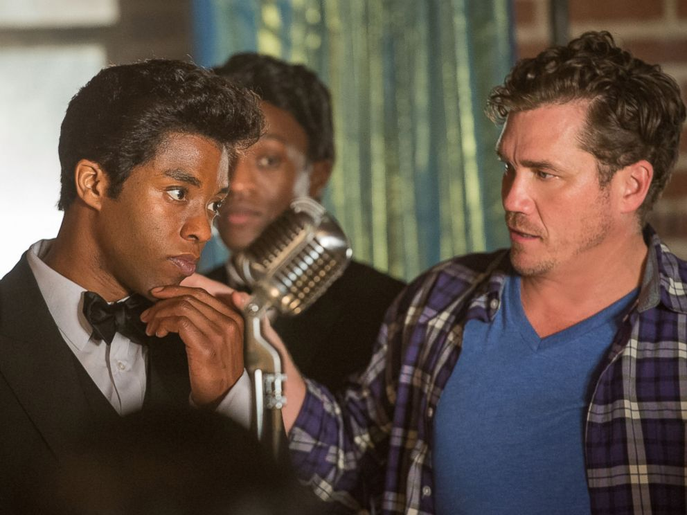 Chadwick Boseman works with director Tate Taylor on the set of Get on Up.