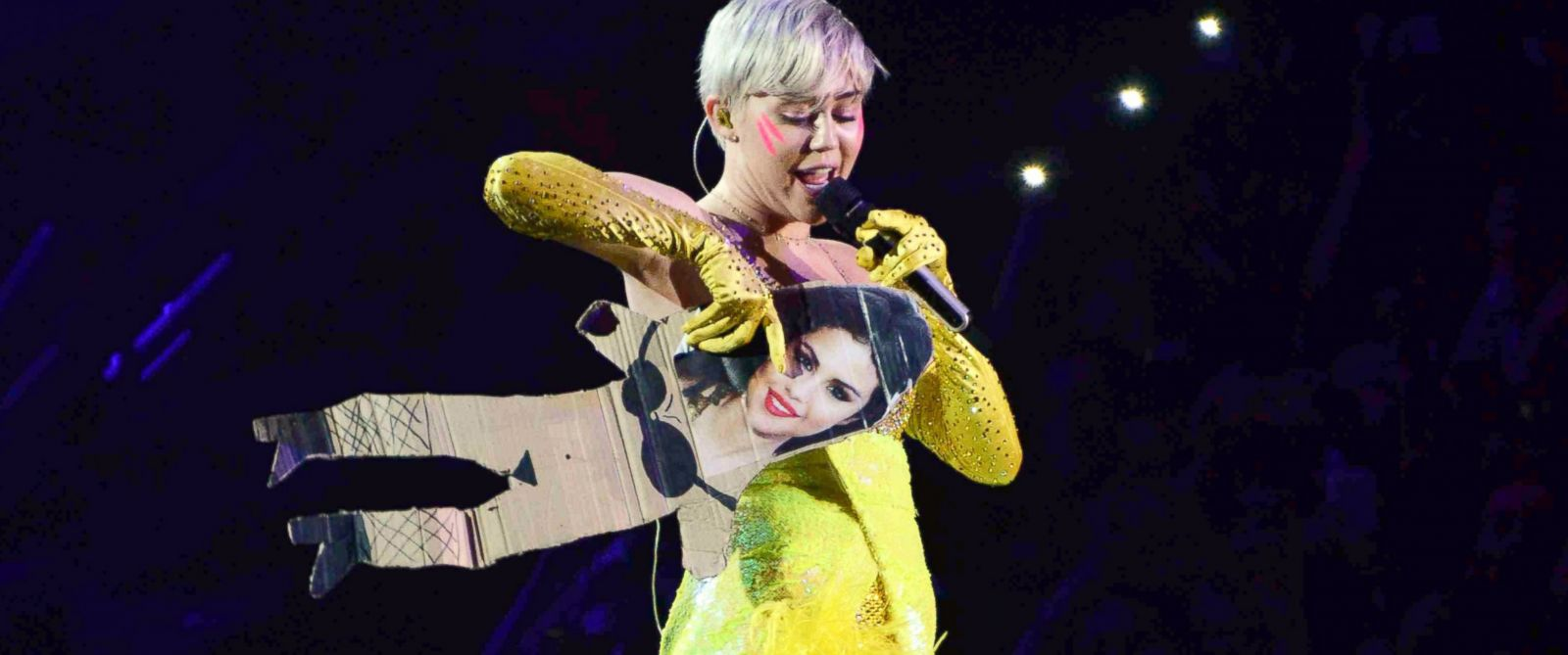 PHOTO: Miley Cyrus holds a cardboard cutout with Selena Gomezs photograph on it during her concert at the Forum in Milan, Italy on June 8, 2014.