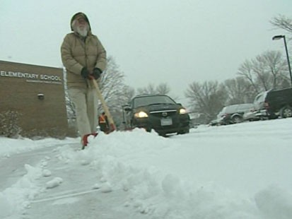 VIDEO: Some one shoveling snow from a sidewalk.