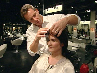A picture of Chris Cuomo cutting someones hair.
