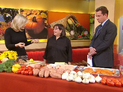 A picture of Diane Sawyer, Ina Garten and Chris Cuomo next to a table of food.