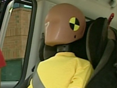 A picture if a crash test dummy in a booster seat.