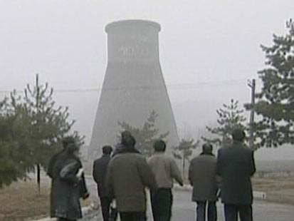 People walking towards cooling tower