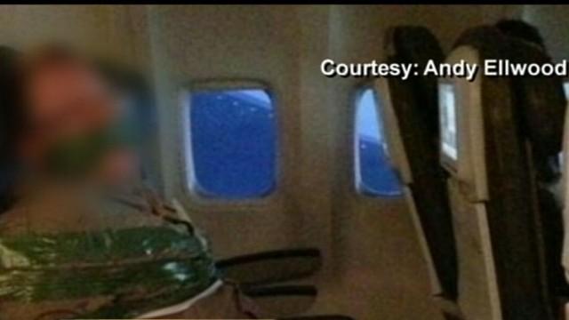 VIDEO: Drunken traveler tied down by fellow passengers on overseas trip.