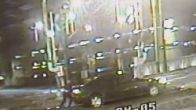 VIDEO: Passersby tried to help get the car off the tracks as a train headed for them.