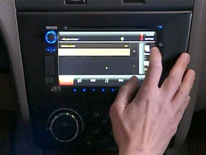 VIDEO: A hand touching a cars computer monitor.