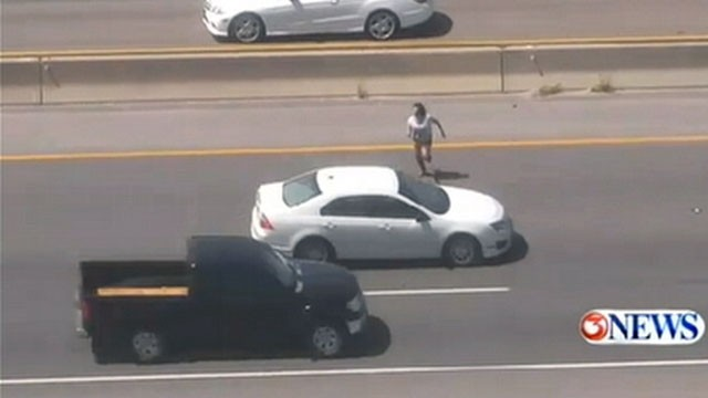 VIDEO: The female suspect ran across a 10-lane highway in Texas and is still on the loose.