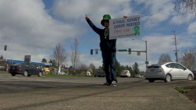 Kevin Gray, of Newberg, Ore., stands beside the highway holding sign asking for kidney donor.