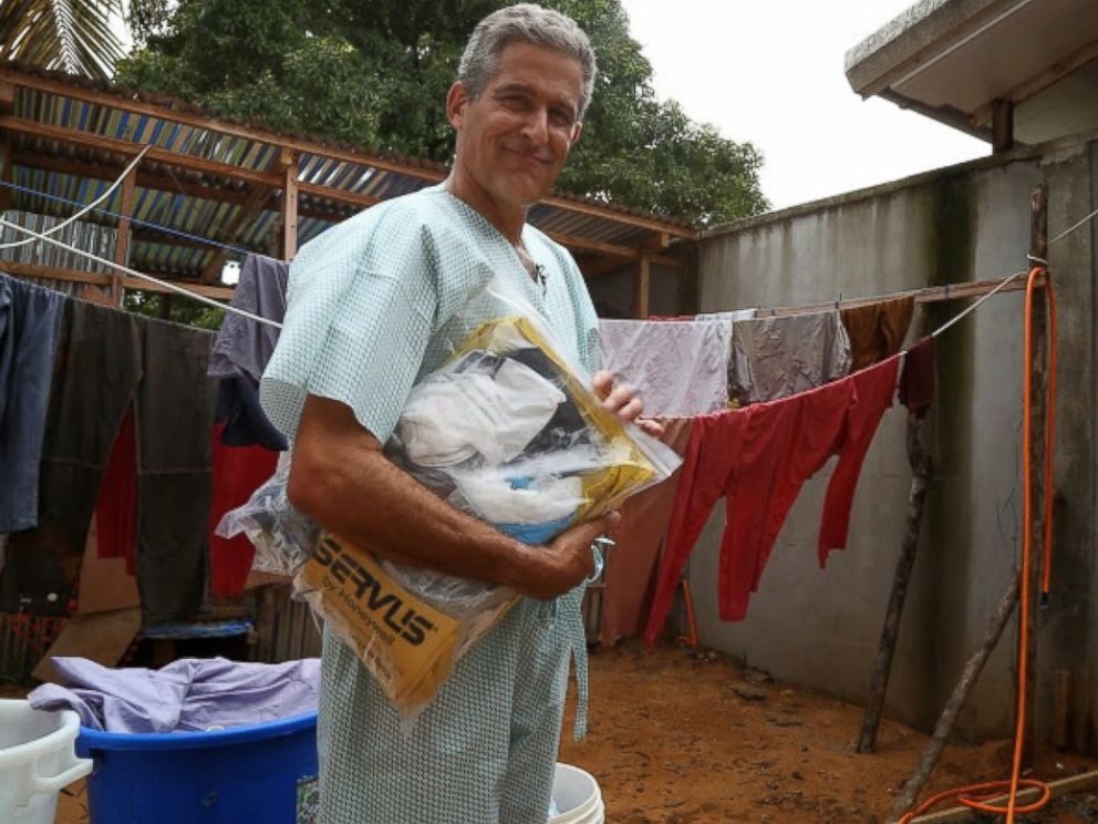 PHOTO: Dr. Besser dons scrubs before putting on several layers of protective gear.
