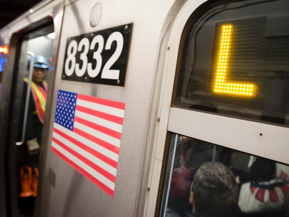 Riders stand inside an L-Train subway car, Thursday, Oct. 23, 2014, in New York.