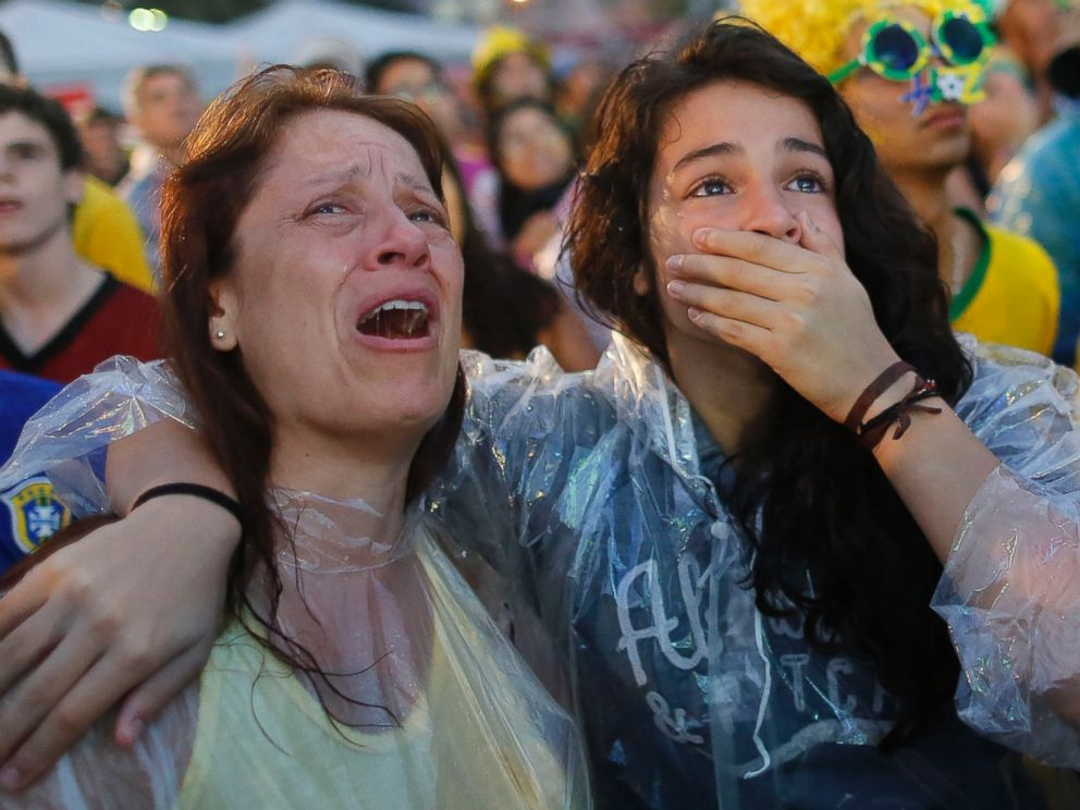 PHOTO: Brazil soccer fans cry as they watch their team lose 7-1 to Germany at a World Cup semifinal match on a live telecast inside the FIFA Fan Fest area on Copacabana beach in Rio de Janeiro, Brazil on July 8, 2014.