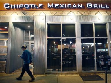 PHOTO: A man walks near a closed Chipotle restaurant, Dec. 7, 2015, in the Cleveland Circle neighborhood of Boston.