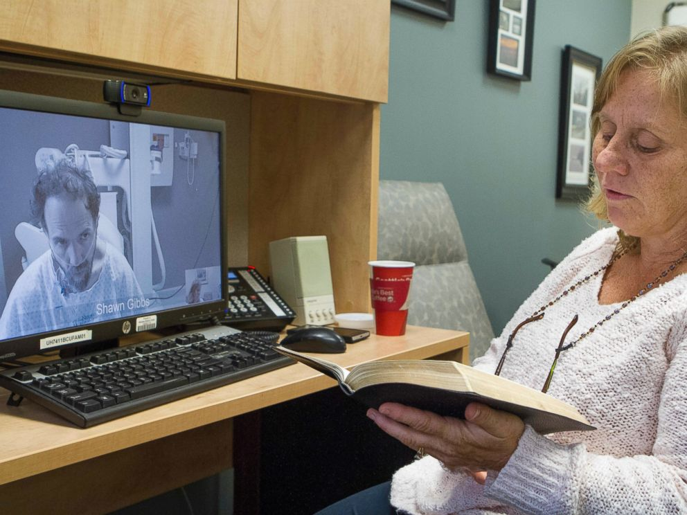 PHOTO: In this Sept. 10, 2014 photo released by the Nebraska Medical Center, Debbie Sacra reads Bible verses to her husband Dr. Richard Sacra via a video link in Omaha, Neb.