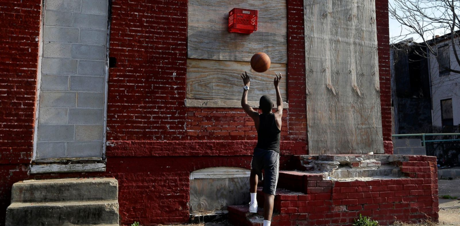 PHOTO: A boy shoots a basketball into a makeshift basket made from a milk crate and attached to a vacant row house in Baltimore, April 8, 2013.