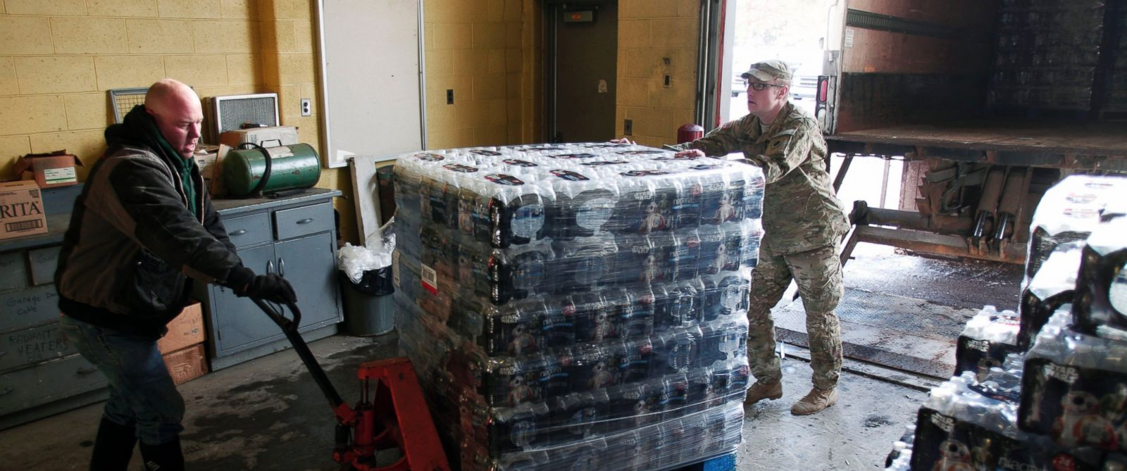 PHOTO: Michigan National Guard Staff Sergeant William Phillips (right), helps a worker unload bottled water in Flint, Michigan, Jan. 13, 2016.