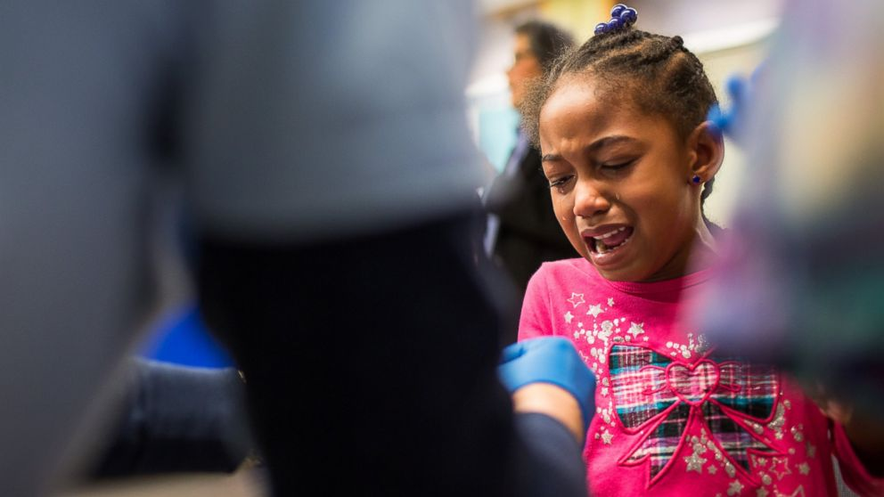 PHOTO: Tears stream down the face of Morgan Walker, age 5 of Flint, as she gets her finger pricked for a lead screening on Jan. 26, 2016 at Eisenhower Elementary School in Flint, Mich.