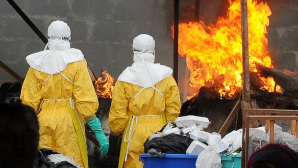 PHOTO: Health care workers wearing full body suits burn infected items at the ELWA Hospital in Monrovia on Aug. 30, 2014.