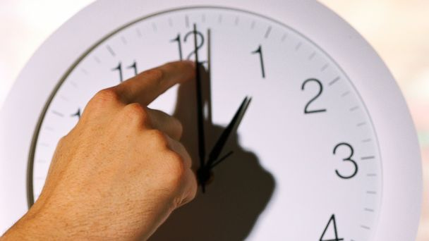 PHOTO: A hand changing time on clock.