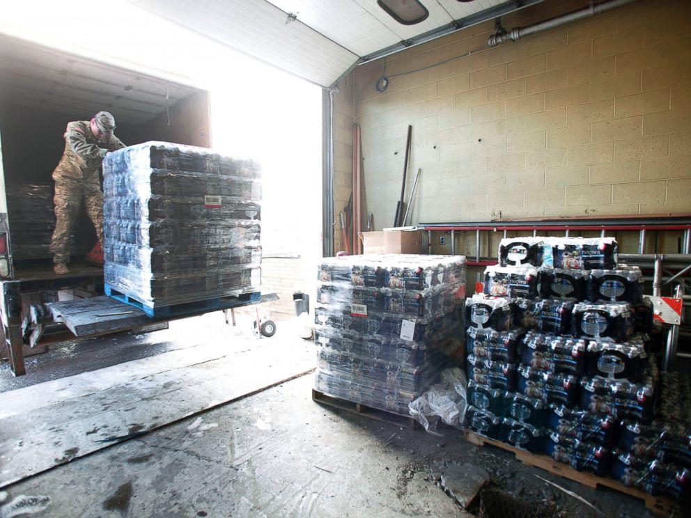 PHOTO: Michigan National Guard Staff Sergeant William Phillips of Birch Run, Michigan, helps unload pallets of bottled water at a Flint Fire Station, Jan. 13, 2016, in Flint, Michigan.